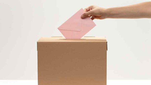 hand-puts-pink-envelope-into-vote-box (1)